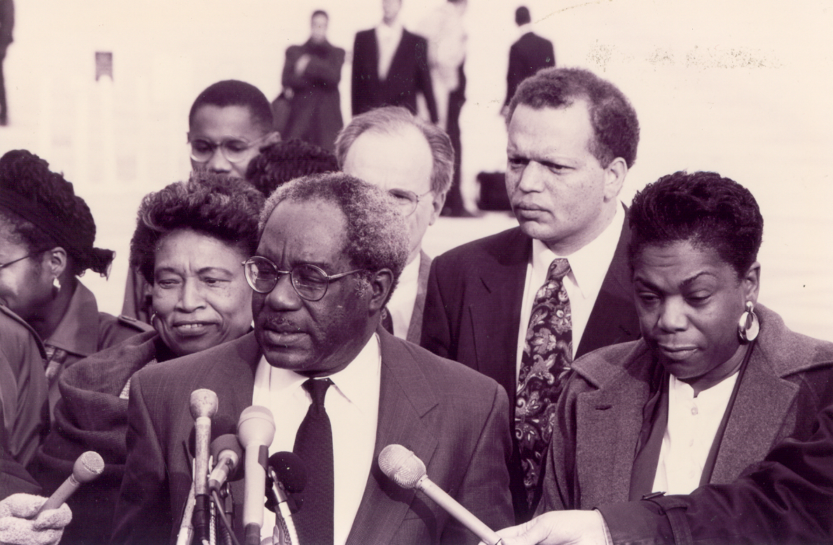 In 1995, on the steps of the United States Supreme Court, after making arguments in the case of Shaw v. Hunt, founding director Julius L. Chambers addresses a reporter. Congressman Cleo Fields, Congresswoman Eva Clayton, attorney J. Gerald Hebert, current director Ted Shaw, and Legal Defense Fund's associate-director counsel Elaine R. Jones stand with him.